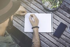 做笔记的行家男学生,写目标在笔记薄,当坐咖啡馆时大阳台  被集中的人文字 免版税库存照片