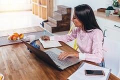 做笔记的被集中的自由职业者妇女由运作在家坐的互联网在桌上 图库摄影