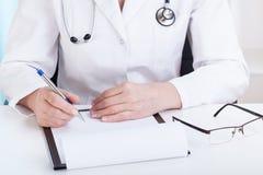 做笔记的医生在办公室 免版税库存图片