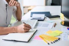 做笔记经营计划和图表设计师有计算机的商人运作的文字在办公室 免版税库存照片