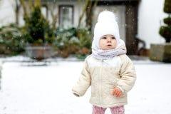 做第一步的可爱的矮小的女婴户外在冬天 学会走的逗人喜爱的小孩 获得的孩子在寒冷的乐趣 图库摄影