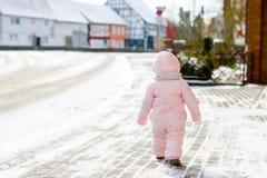 做第一步的可爱的矮小的女婴户外在冬天 学会走的逗人喜爱的小孩 获得的孩子在寒冷的乐趣 免版税库存照片