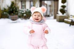 做第一步的可爱的矮小的女婴户外在冬天 学会走的逗人喜爱的小孩 图库摄影