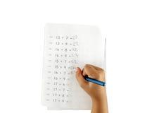 做算术家庭作业的小女孩的手隔绝在白色背景 库存照片