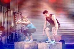 做箱子的夫妇在健身房跳跃 库存图片