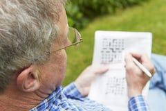 做纵横填字游戏的老人在庭院里 免版税库存照片