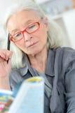 做纵横填字谜的老妇人 免版税库存照片