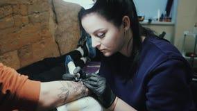 做纹身花刺的深色的女性tattooer在她的有枪的客户的人的胳膊 主要工作 年轻女商人 股票视频