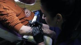 做纹身花刺的深色的女性tattooer在她的有枪的客户的人的胳膊 主要工作 年轻女商人 影视素材