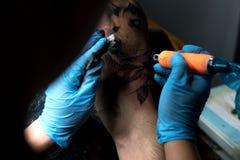 做纹身花刺的男性文身的人在肩膀,特写镜头 库存照片