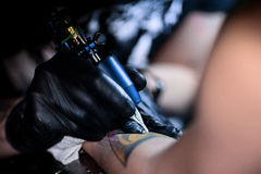 做纹身花刺的纹身花刺艺术家 大师运作在专业机器和在不育的黑手套 免版税图库摄影