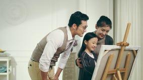 做绘画的亚裔妈妈和爸爸观看的帮助的女儿 股票录像