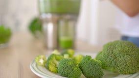 做绿色硬花甘蓝蔬菜汁的榨汁器 关闭投入菜的Juicing机器和妇女手在汁液 影视素材