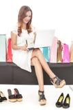 做网上交易和坐在shoppin之间的少妇 库存照片