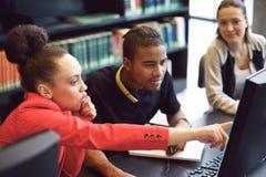 做网上研究的小组学生在图书馆里 免版税库存照片