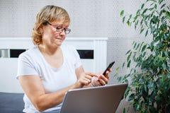做网上购物的一名中年妇女使用智能手机和膝上型计算机 免版税库存图片