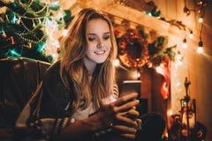 做网上购物的一名年轻微笑的妇女的画象在圣诞节前 免版税图库摄影