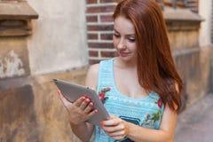 做网上购物的年轻俏丽的女孩使用片剂 都市bac 免版税库存照片