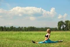 做美丽的体育的妇女舒展健身锻炼在城市公园在绿草 免版税库存照片