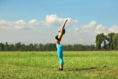 做美丽的体育的妇女舒展健身锻炼在城市公园在绿草 图库摄影