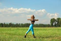 做美丽的体育的妇女舒展健身锻炼在城市公园在绿草 免版税图库摄影