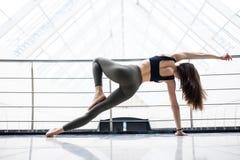 做美丽的asana的瑜伽类的少妇行使 在健身俱乐部的健康生活方式 舒展asana 库存图片