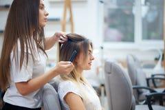 做美发师的侧视图鼓胀对美容院的顾客 免版税库存照片
