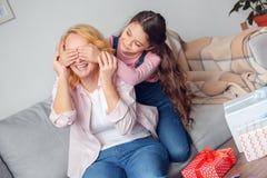 做老婆婆的孙女和祖母在家庆祝坐的女孩惊奇 库存图片