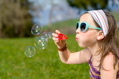 做肥皂泡的一个小女孩 免版税图库摄影