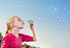 做肥皂泡的女孩外面 免版税图库摄影