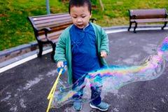 做肥皂泡的小男孩 免版税库存图片
