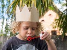 做肥皂泡的小白肤金发的男孩 免版税库存照片
