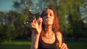 做肥皂泡的年轻俏丽的成人女孩正面图  与橙色叶子的美丽的树 股票视频