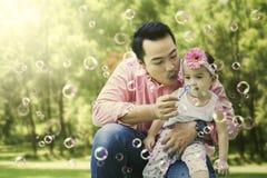 做肥皂泡的父亲和女儿 免版税库存照片