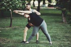做肥胖的妇女舒展与教练员的锻炼 库存照片