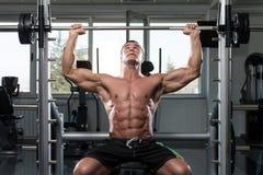 做肩膀的男性爱好健美者重量级的锻炼 库存图片