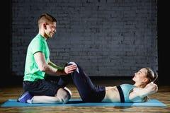 做胃肠咬嚼的妇女按在席子的锻炼有她的在健身房的体育男性教练员的 免版税库存照片