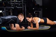 做胃肠咬嚼的妇女按在席子的锻炼有她的体育男性教练员的 免版税库存图片
