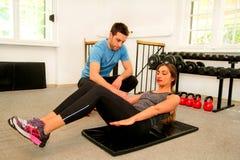 做胃锻炼的运动的人民在健身房俱乐部 免版税库存图片