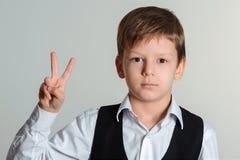 做胜利标志的学生男孩 库存图片