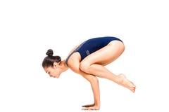 做胳膊平衡瑜伽姿势的年轻亭亭玉立的灵活的妇女 免版税库存图片