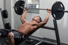 做胸口的肌肉人卧推锻炼 免版税库存照片