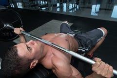 做胸口的年轻人卧推锻炼 免版税图库摄影