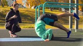 做脊椎的年轻灵活的人锻炼在运动场 影视素材
