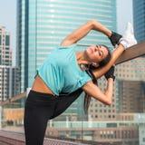 做脚的健身妇女在城市举起了在一条长凳的俯卧撑 行使运动的女孩户外 库存照片