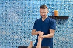 做脚的按摩在温泉沙龙的男性医生正面图 免版税图库摄影