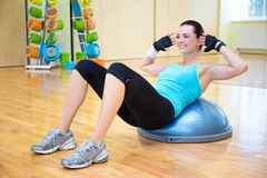 做腹肌的妇女锻炼在bosu球 免版税图库摄影