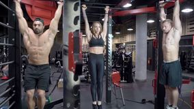 做腹肌锻炼的小组年轻体育人民使用在健身房的一架单杠 股票视频