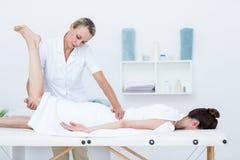 做腿按摩的生理治疗师 免版税库存照片