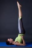 做腿的年轻美丽的运动的女孩上升在灰色的锻炼 库存照片